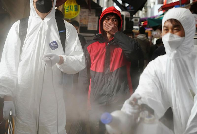 A man reacts as employees from a disinfection service company sanitize a traditional market in Seoul on Feb. 26 | Hong-Ji Kim—REUTERS