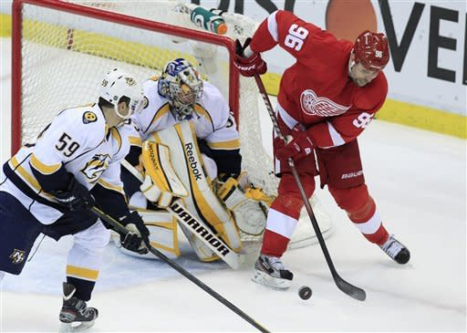 Detroit Red Wings left wing Tomas Holmstrom (96) of Sweden tries hitting the puck past Nashville Predators goalie Pekka Rinne (35) of Finland and defenseman Roman Josi (59) of Switzerland during the second period of Game 4 of an NHL hockey Stanley Cup first-round playoff series in Detroit, Tuesday, April 17, 2012. (AP Photo/Carlos Osorio)