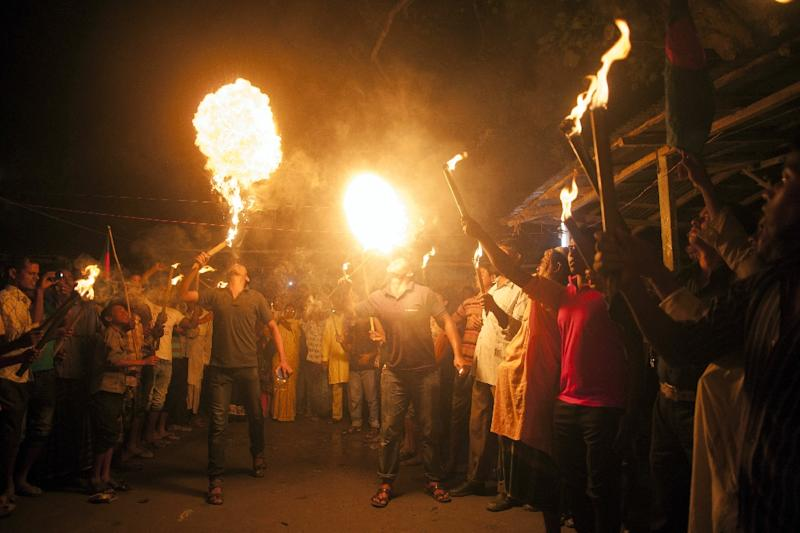 Former Indian enclave residents look on as others perform fire eating tricks at Dasiarchhara, Kurigram in Bangladesh, August 1, 2015 (AFP Photo/Suvra Kanti Das)
