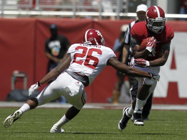 Alabama running back T.J. Yeldon (4) runs for a first down around defensive back Landon Collins (26) during Alabama's A-Day NCAA college football spring game on Saturday, April 19, 2014, in Tuscaloosa, Ala. (AP Photo/Butch Dill)