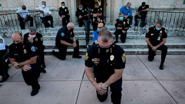PHOTO: Police officers kneel during a rally in Coral Gables, Florida, May 30, 2020, in response to the recent death of George Floyd, an unarmed black man who died while being arrested and pinned to the ground by a Minneapolis police officer. (Eva Marie Uzcategui/AFP via Getty Images)