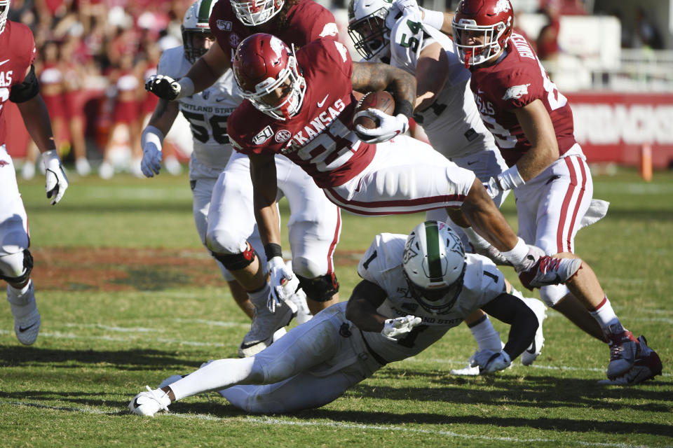 Arkansas running back Devwah Whaley is tripped up by Portland State defender Romeo Gunt during the second half of an NCAA college football game Saturday, Aug. 31, 2019 in Fayetteville, Ark. (AP Photo/Michael Woods)