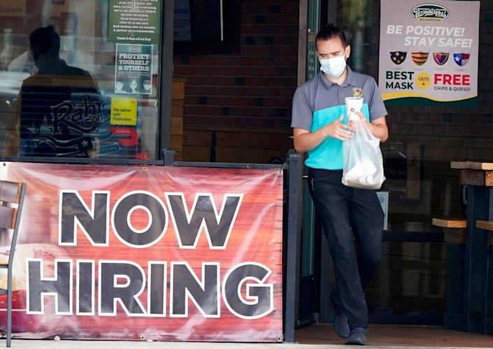 """A customer wears a face mask while carrying a takeout order past a """"now hiring"""" sign at a Texas eatery."""