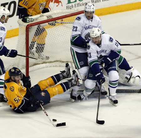 FILE PHOTO: Nashville Predators Austin Watson (52) tries to shoot on goal as he falls to the ice as Vancouver Canucks Steve Pinizzotto (13) and Alexander Edler(23) defend during the first period of their NHL hockey game in Nashville, Tennessee April 15, 2013. REUTERS/Harrison McClary