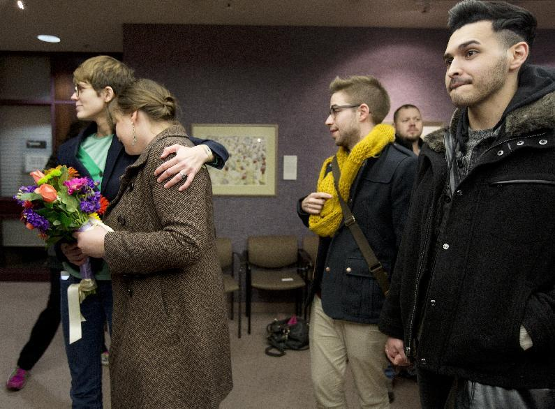Same-sex couples Natalie Dicou, left, and Nichole Christensen, middle left, and James Goodman, middle right, and Jeffrey Gomez, right, wait in line to get a marriage license at the Salt Lake County Clerk's Office in Salt Lake City on Friday, Dec. 20, 2013. A federal judge ruled on Friday that Utah's ban on same-sex marriage is unconstitutional. (AP Photo/Kim Raff)
