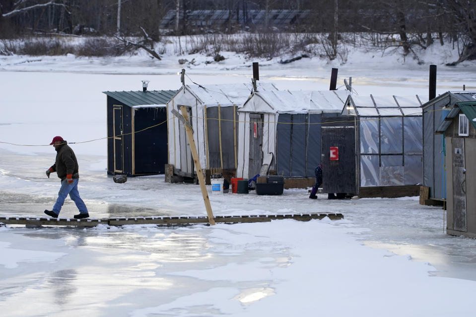 FILE - Clem Tome walks cross a temporary bridge on the ice at Leighton's Smelt Camps, Wednesday, Feb. 10, 2021, in Bowdoinham, Maine. A lack of ice in cold weather states this year has made it difficult for scientists to study the rainbow smelt population. (AP Photo/Robert F. Bukaty)