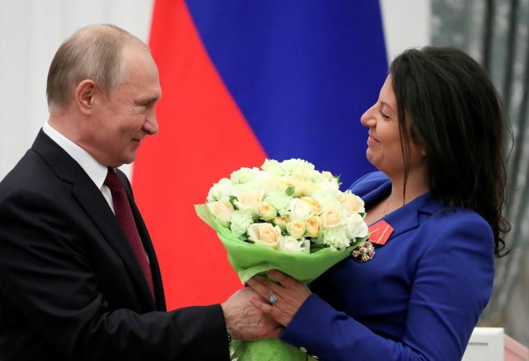 "Britain has said it will bar Sputnik news and RT from a global conference on media freedom in London; in this image from May 23 2019, Russia's President Vladimir Putin presents flowers to editor-in-chief of Russian broadcaster RT Margarita Simonyan after awarding her with the ""Order of Alexander Nevsky"""