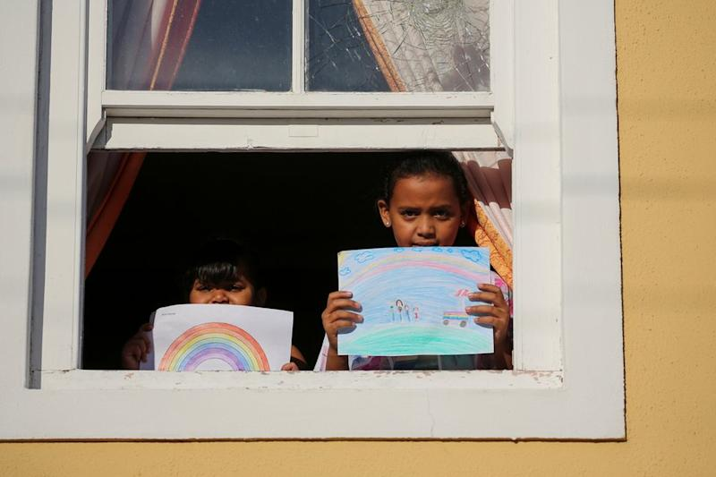 Two children stand at the window holding their drawing of what they miss most - their illustrations show rainbows and ice-cream vans.