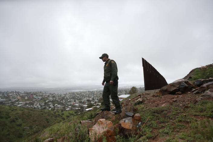 FILE - In this Feb. 5, 2019, file photo, Border Patrol agent Vincent Pirro looks on near where a border wall ends that separates the cities of Tijuana, Mexico, left, and San Diego, in San Diego. The government is working on replacing and adding fencing in various locations, and Trump in February declared a national emergency to get more funding for the wall. (AP Photo/Gregory Bull, File)