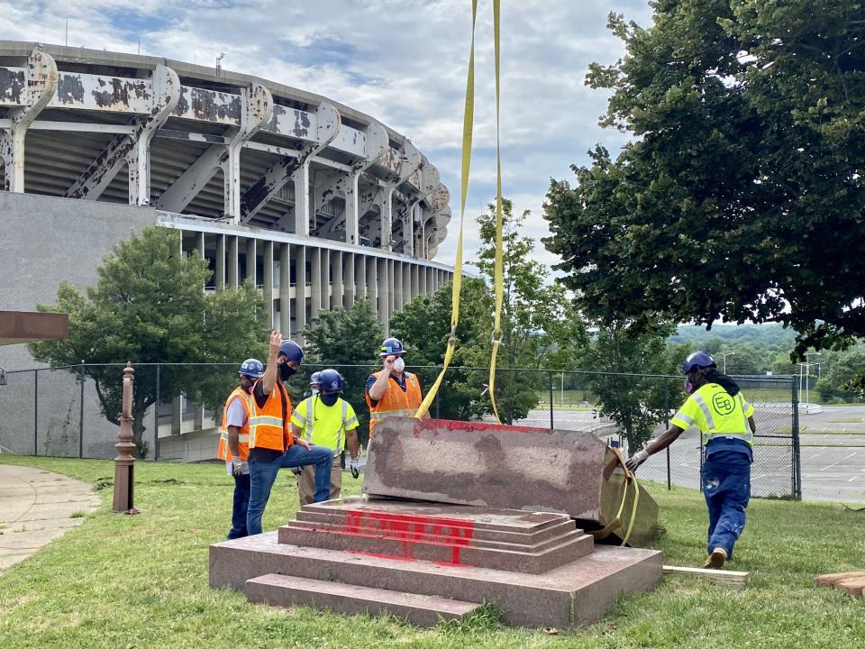 A crew removes the George Preston Marshall memorial outside RFK Stadium on Friday morning. (Rick Maese/Twitter)