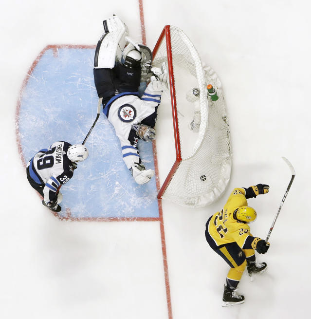 Nashville Predators left wing Kevin Fiala (22), of Switzerland, celebrates after scoring the winning goal against Winnipeg Jets goalie Connor Hellebuyck, center, during the second overtime in Game 2 of an NHL hockey second-round playoff series Sunday, April 29, 2018, in Nashville, Tenn. The Predators won 5-4 to tie the series 1-1. At left is Jets defenseman Toby Enstrom (39), of Sweden. (AP Photo/Mark Humphrey)