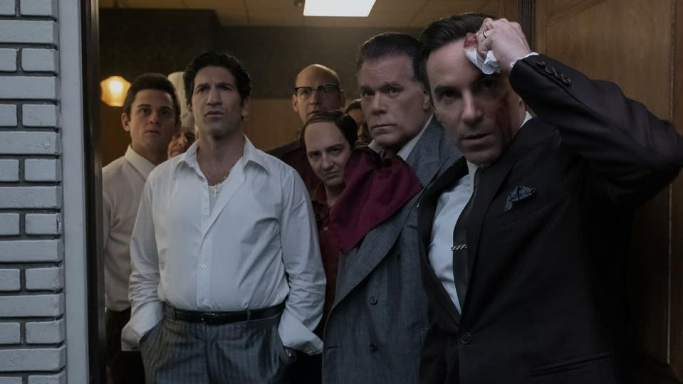 The many members of the DiMeo Crime Family, standing in a doorway looking out, in the movie The Many Saints of Newark.