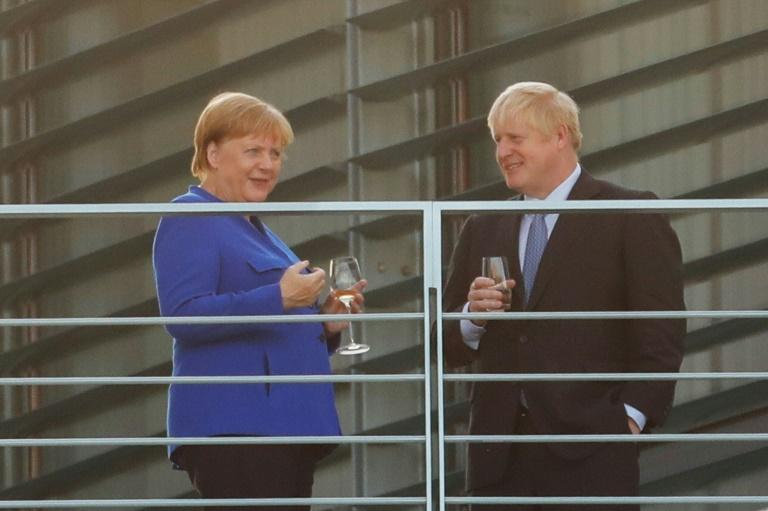 German Chancellor Angela Merkel and British Prime Minister Boris Johnson have a drink on the terrace at the Chancellery on his first foreign visit since taking office