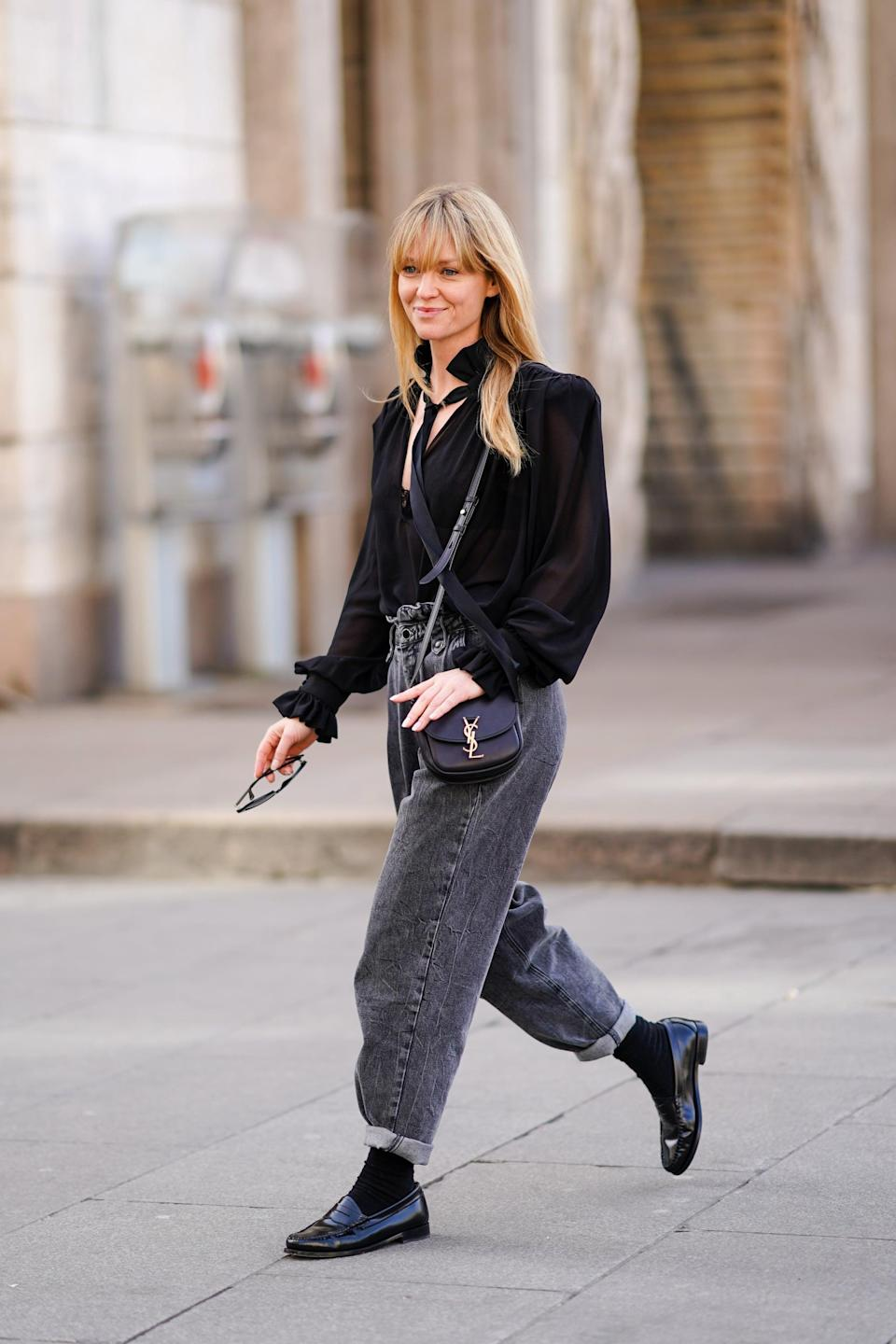 <p>An all-black outfit with baggy jeans can look preppy and polished with a blouse and loafers (with socks!) in the mix. </p>