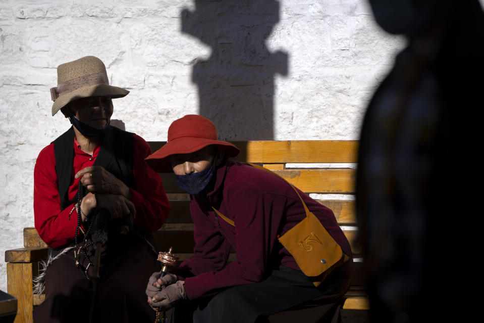Members of the Buddhist faithful hold beads and a prayer wheel as they sit on a bench outside the Jokhang Temple in Lhasa in western China's Tibet Autonomous Region, Tuesday, June 1, 2021, as seen during a government organized visit for foreign journalists. High-pressure tactics employed by China's ruling Communist Party appear to be finding success in separating Tibetans from their traditional Buddhist culture and the influence of the Dalai Lama. (AP Photo/Mark Schiefelbein)