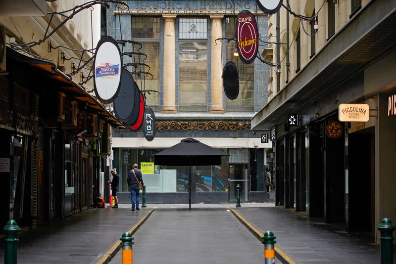 A man walks down an empty city laneway on the first day of a five-day COVID-19 lockdown in Melbourne