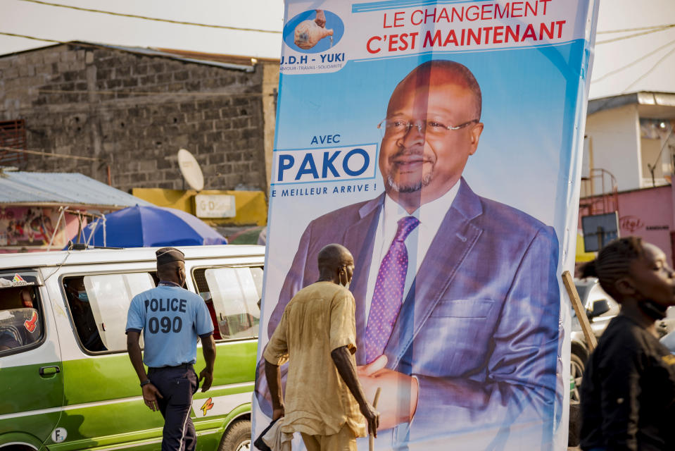 People walk past an election poster featuring opposition presidential candidate Guy Brice Parfait Kolelas in central Brazzaville, Congo, Sunday March 7, 2021. Elections on Sunday March 21 will see President Denis Sassou N'Guesso poised to extend his tenure as one of Africa's longest serving leaders, 36 years, amid opposition complaints of interference with their campaigns. (AP Photo/Lebon Chansard Ziavoula)