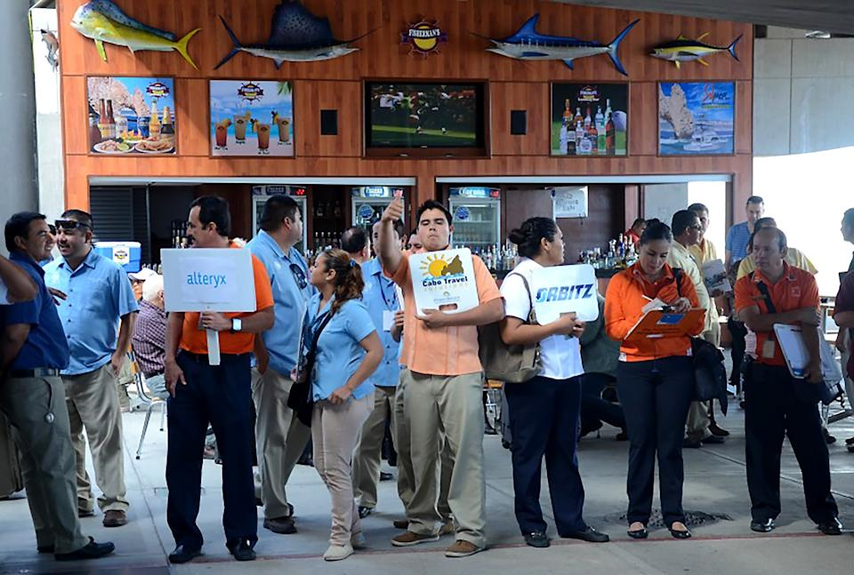 """Los Cabos tourism officials say new health and distancing measures will make arrivals in Baja California Sur much different than in years past. Here, tour guides and drivers await arrivals at the Los Cabos International Airport in February 2015. <span class=""""copyright"""">(Christopher Reynolds/Los Angeles Times)</span>"""