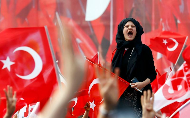 Supporters of Turkish President Erdogan wave national flags during a rally for the upcoming referendum - Credit: REUTERS/Umit Bektas