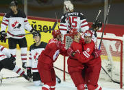 Yevgeni Timkin , centre, Artyom Shvets-Rogovoi, left, and Vladislav Kamenev of Russia celebrate a goal against Darcy Kuemper of Canada during the Ice Hockey World Championship quarterfinal match between Russia and Canada at the Olympic Sports Center in Riga, Latvia, Thursday, June 3, 2021. (AP Photo/Roman Koksarov)