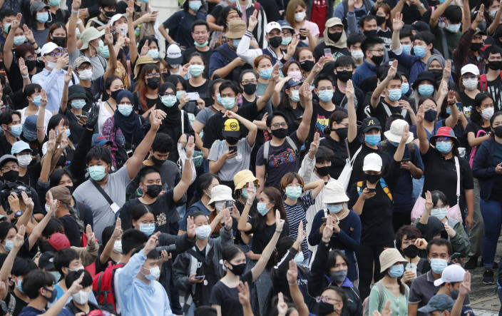 Pro-democracy demonstrators flash three-fingered salute during an anti-government protest, at Victory Monument in Bangkok, Thailand, Sunday, Oct. 18, 2020. Thai police on Sunday declined to say whether they were taking a softer approach toward student anti-government demonstrations, after several mass rallies attracting thousands of protesters ended peacefully in Bangkok on Saturday. (AP Photo/Sakchai Lalit)
