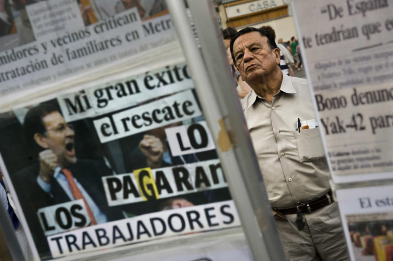 A man reads news paper collages during a trade unions demonstration against the government Economic measures and new labor reforms in central Madrid, Wednesday, June 20, 2012. After years of insisting its banks were among the healthiest in Europe, Spain recently acknowledged it will need a rescue package. But investors are now more concerned that the country itself may have to be bailed out and this could seriously test the strength of the entire European Union's finances. Papers read 'My biggest success the rescue, will be paid by workers'.(AP Photo/Daniel Ochoa de Olza)
