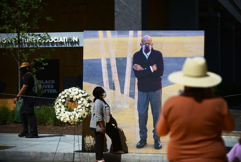 <p>A woman stands in front of a large photograph of Lewis, taken at his last public appearance. Lewis visited the newly renamed Black Lives Matter Plaza in Washington, D.C. last month. </p>
