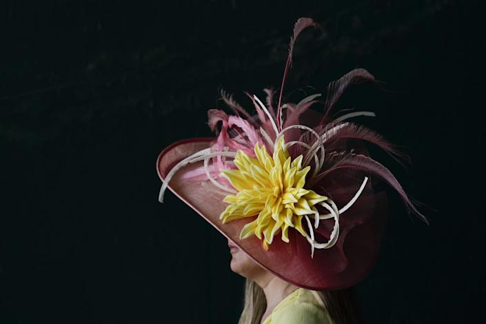 A woman wears a pink brimmed hat with a large yellow flower and pink feathers on it.