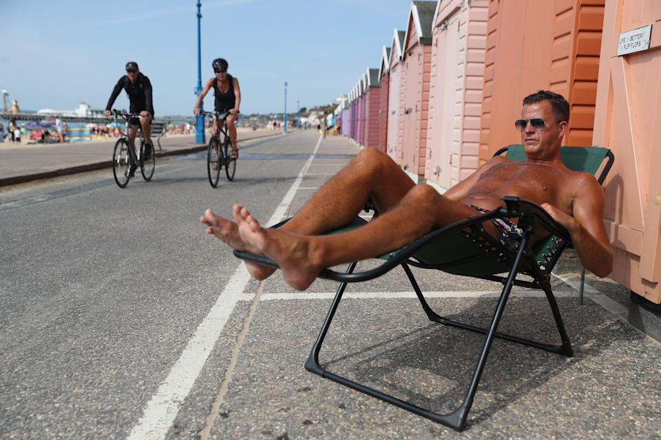 Stuart (no surname given) enjoys the hot weather outside a beach hut at Bournemouth beach in Dorset. (Photo: PA)