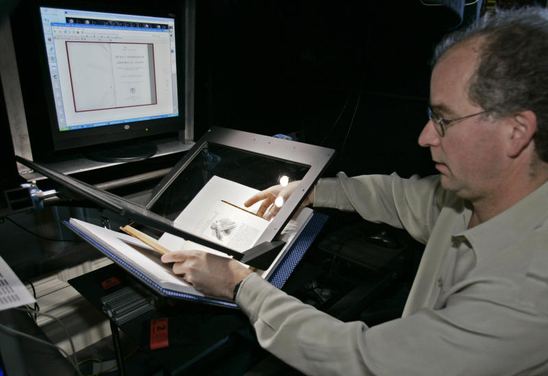FILE-On this Monday, Dec. 18, 2006, file photo, Internet Archive founder Brewster Kahle prepares a book for digital scanning in San Francisco. Google and U.S. publishers settled a longstanding dispute over Google's book-scanning project Thursday, Oct. 4, 2012. Google already has scanned more than 20 million books. Publishers and authors sued, saying the project violated their copyrights. (AP Photo/Ben Margot)