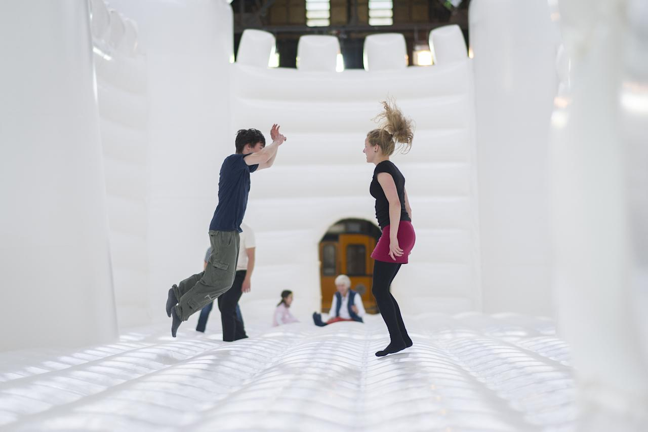 "BERLIN, GERMANY - JUNE 27: Visitors jump in the ""White Bouncy Castle"" of installation artist William Forsythe on June 27, 2013 in Berlin, Germany. The work is a giant, inflatable white castle that Forsythe says encourages people to dance the moment they step into it. ""White Bouncy Castle"" will be open to visitors at Lokhalle Schoeneberg until July 14 and is part of the ""Foreign Affairs"" series of Berliner Festspiele. (Photo by Timur Emek/Getty Images)"