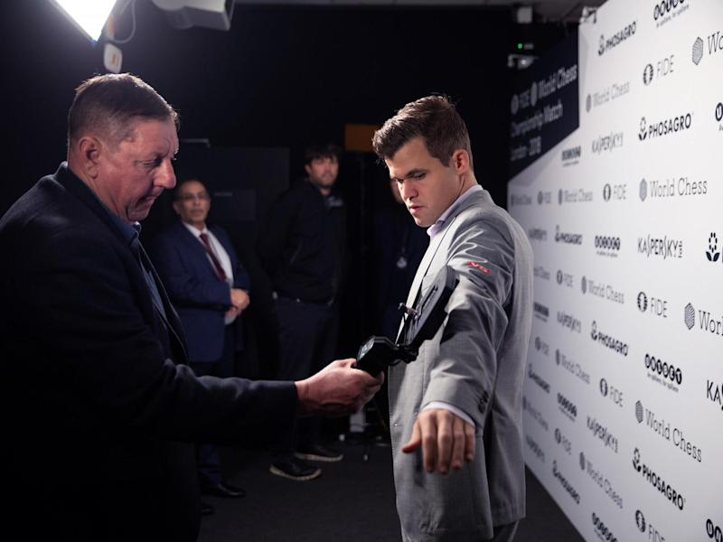 A member of security staff scans Magnus Carlsen as he enters the venue: Pinkerton