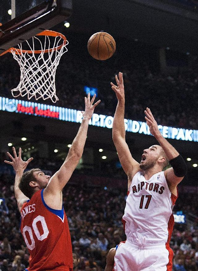 Toronto Raptors' Jonas Valanciunas, right, shoots the ball against the Philadelphia 76ers' Spencer Hawes during the first half of an NBA basketball game in Toronto on Friday, Dec. 13, 2013. (AP Photo/The Canadian Press, Aaron Vincent Elkaim)