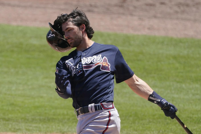Atlanta Braves shortstop Dansby Swanson (7) loses his helmet as he swings during the fourth inning of a spring training baseball game against the Boston Red Sox Tuesday, March 30, 2021, in Fort Myers, Fla. (AP Photo/John Bazemore)