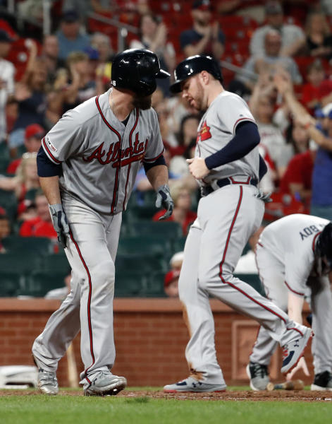 Atlanta Braves' Brian McCann, left, takes his base on a bases-loaded walk as Freddie Freeman scores during the 10th inning of a baseball game against the St. Louis Cardinals, Sunday, May 26, 2019, in St. Louis. (AP Photo/Jeff Roberson)