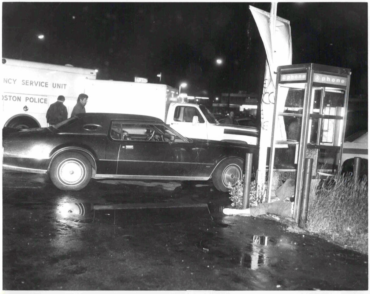 """This undated black and white photo released by the U.S. Attorney's Office and presented as evidence Wednesday, June 19, 2013, during the trial of James """"Whitey"""" Bulger in U.S. District Court in Boston, shows a crime scene where a victim was shot to death in a telephone booth. Bulger, the reputed former head of the mostly Irish-American Winter Hill Gang based in South Boston, is accused of playing a role in 19 killings during the 1970s and '80s. (AP Photo/U.S. Attorney's Office)"""