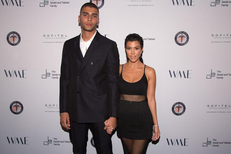 Younes Bendjima steps out in style in a black suit and pant with the love of his life, Kourtney Kardashian in a low-cut new dress that leaves nothing to imagination.