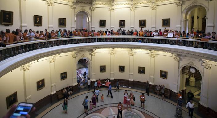 """A large crowd, many wearing Planned Parenthood T-shirts that read """"Stand with Texas Woman,"""" wait in line to enter the house chambers at the Texas State Capitol in Austin, Texas on Sunday, June 23, 2013. More than 600 women's rights protesters crowded into the Texas Capitol to watch Democrats begin a series of parliamentary maneuvers to stop the Republican majority from passing some of the toughest abortion restrictions in the country. (AP Photo/Austin American-Statesman/Statesman.com, Ricardo B. Brazziell)"""