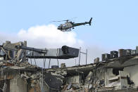 A Miami-Dade Police helicopter flies over the Champlain Towers South Condo after the multistory building partially collapsed, Thursday, June 24, 2021, in Surfside, Fla. (David Santiago/Miami Herald via AP)