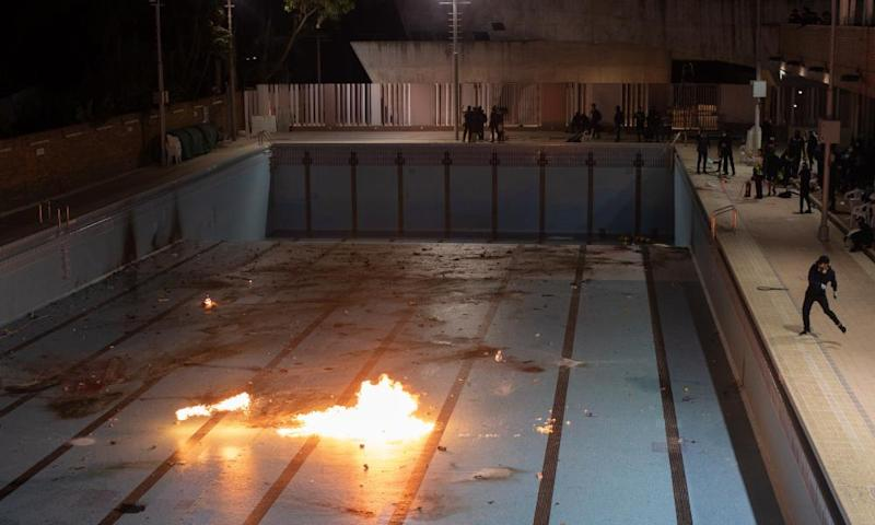 Protesters at a Hong Kong university throw Molotov cocktails into an empty swimming pool.