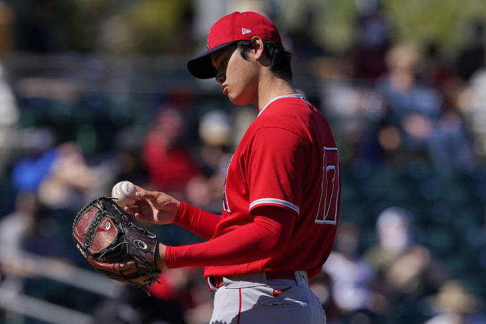 Los Angeles Angels pitcher Shohei Ohtani looks at the baseball after a pitch against the Oakland Athletics during the first inning of a spring training baseball game, Friday, March 5, 2021, in Mesa, Ariz. (AP Photo/Matt York)