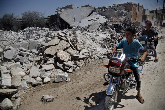 File - In this Wednesday, Aug. 8, 2012 file photograph, Syrians on motorcycles look at the damage of a destroyed house after it was hit by an air strike killing six Syrians in town of Tal Rifat on the outskirts of Aleppo city, Syria. In recent months, Syria's rebels have extended control over a large swath of territory in the northeastern corner of the country after forcing the army from town after town in a string of bloody street battles. (AP Photo/ Khalil Hamra, File)