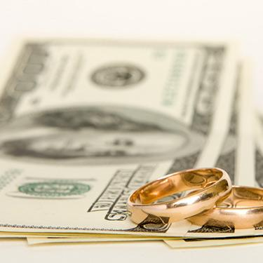Gold-wedding-bands-stacked-on-money_web