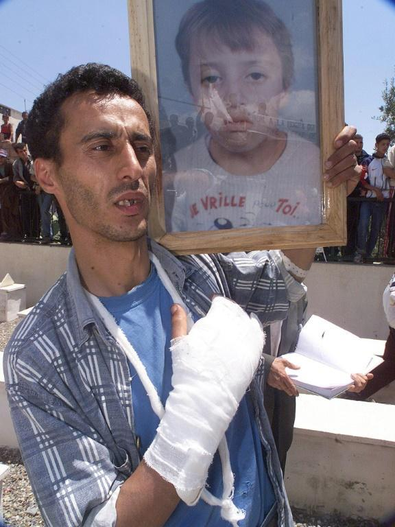 A wounded Berber man, pictured in May 2001, holds the picture of a 13-year-old boy who was shot dead in clashes in Takriet, near Bejaia, in the Kabylie region