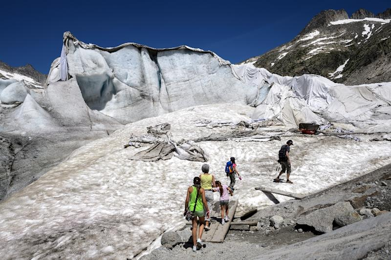 Tourists in July 2015 walk towards an ice cave next to insulating foams wrapping up the Rhone Glacier to prevent it shrinking under the summer sun (AFP Photo/Fabrice Coffrini)