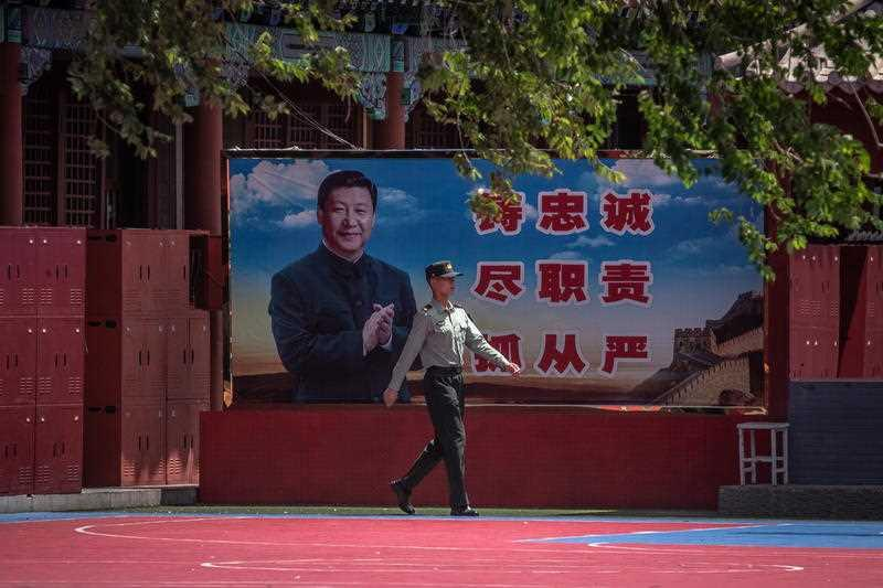 A Chinese People's Liberation Army (PLA) soldier walks past a banner depicting Chinese President Xi Jinping near the Forbidden City, in Beijing, China.
