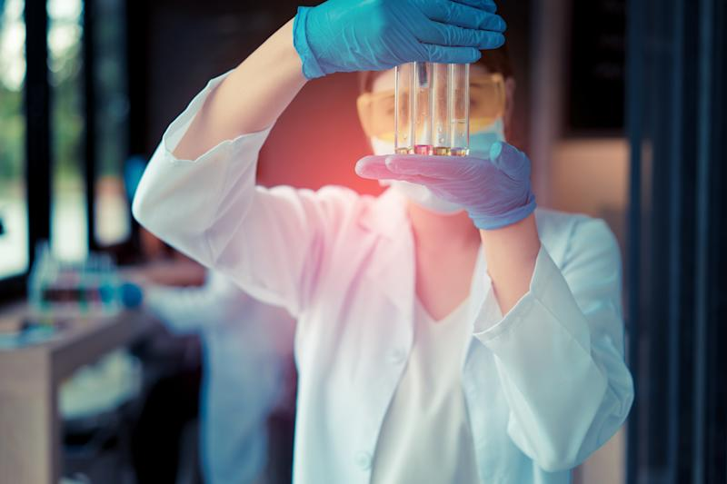 Lab worker holding test tubes in front of their face.