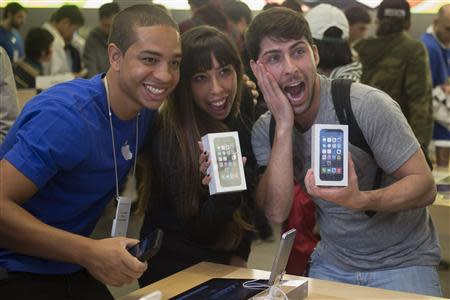 Alejandro de Rosa (R) and Melisa Racineti of Buenos Aires, Argentina pose with their new Apple iPhone 5s phones with Apple employee Jay at the Apple Retail Store on Fifth Avenue in Manhattan, New York September 20, 2013. Apple Inc's newest smartphone models hit stores on Friday in many countries across the world, including Australia and China. REUTERS/Adrees Latif