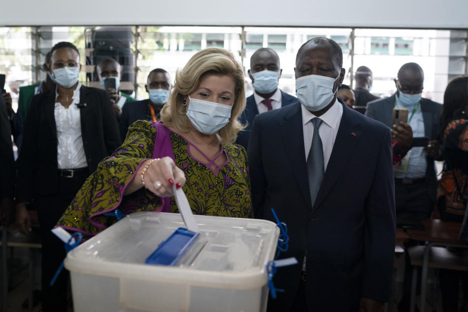 Dominique Ouattara casts her vote as her husband, the Ivory Coast President Alassane Ouattara, right, looks on at a polling station during presidential elections in Abidjan, Ivory Coast, Saturday, Oct. 31, 2020. Tens of thousands of security forces are deployed across Ivory Coast on Saturday as the leading opposition parties boycotted the election, calling President Ouattara's bid for a third term illegal. (AP Photo/Leo Correa)