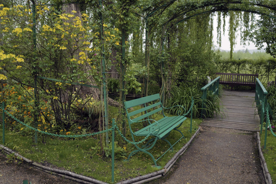 The green bench in the Japanese-inspired water garden of Claude Monet's house, French impressionist painter who lived from 1883 to 1926, waits ahead of the re-opening, in Giverny, west of Paris, Monday May 17, 2021. Lucky visitors who'll be allowed back into Claude Monet's house and gardens for the first time in over six months from Wednesday will be treated to a riot of color, with tulips, peonies, forget-me-nots and an array of other flowers all competing for attention. (AP Photo/Francois Mori)